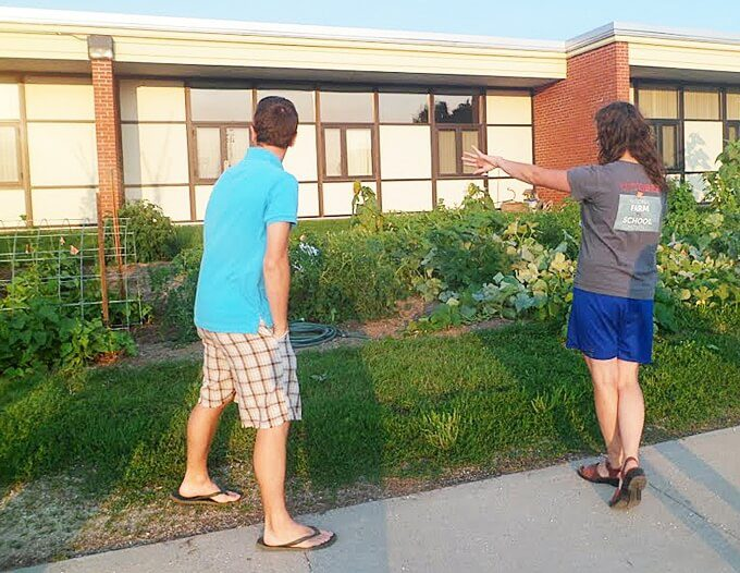 Kayla Koether (right) showed MFL MarMac school board members and staff the Monona Center Elementary Garden at the Aug. 12 school board meeting. (Photo by Audrey Posten)